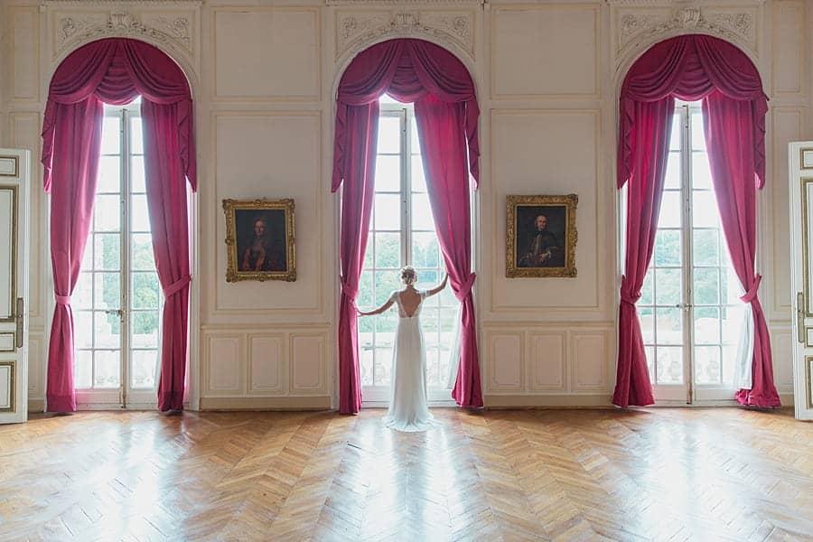 La marié joue avec les rideaux du château