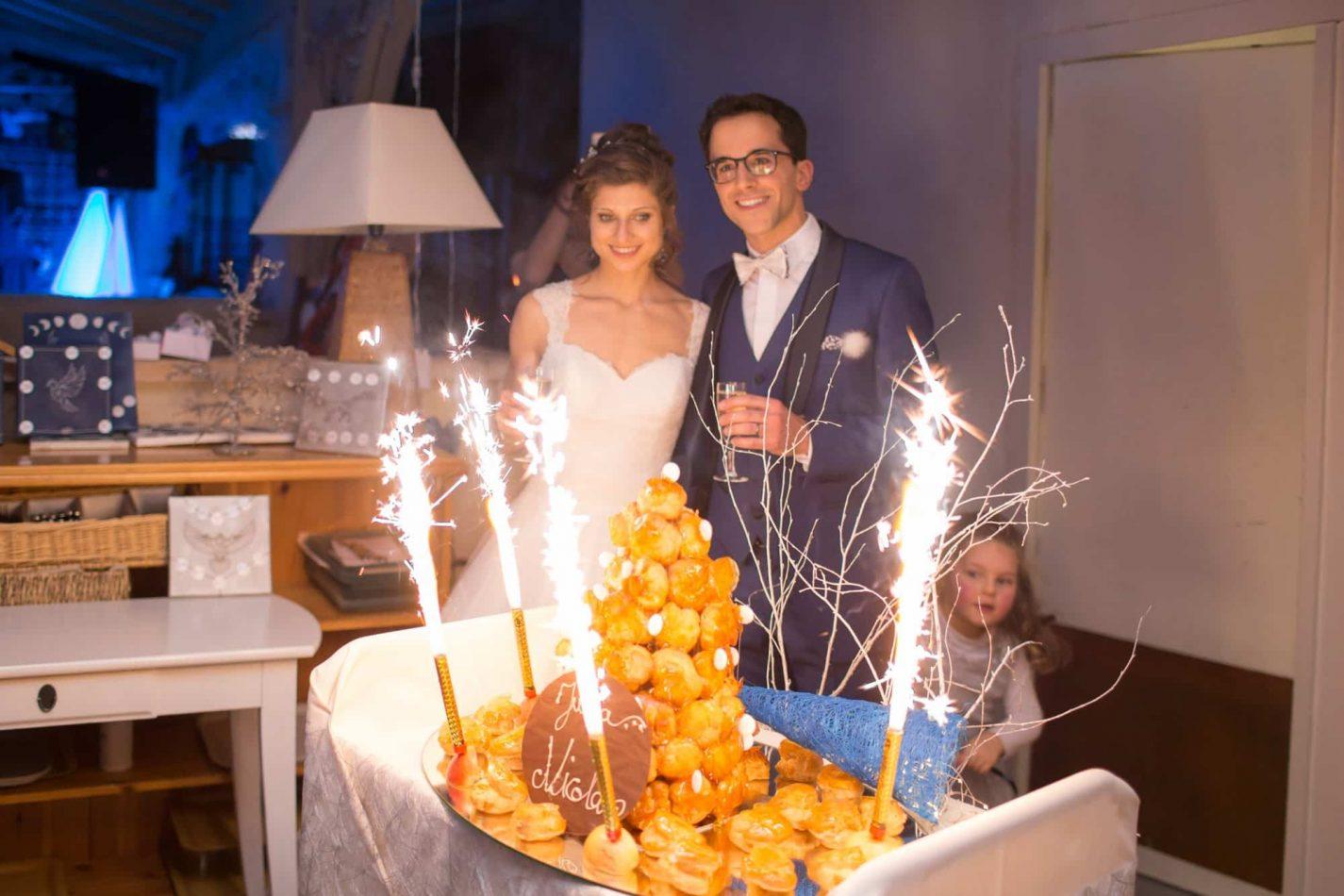 la jolie pièce montée avec les mariés souriants derrière