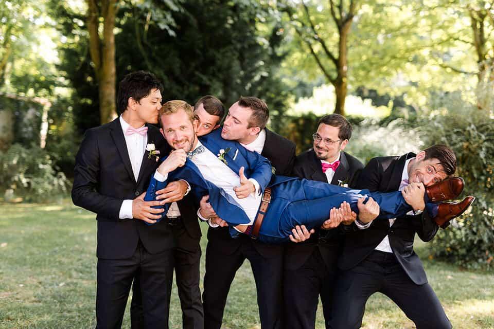 le marié se fait plaisir pendant la photo de groupe