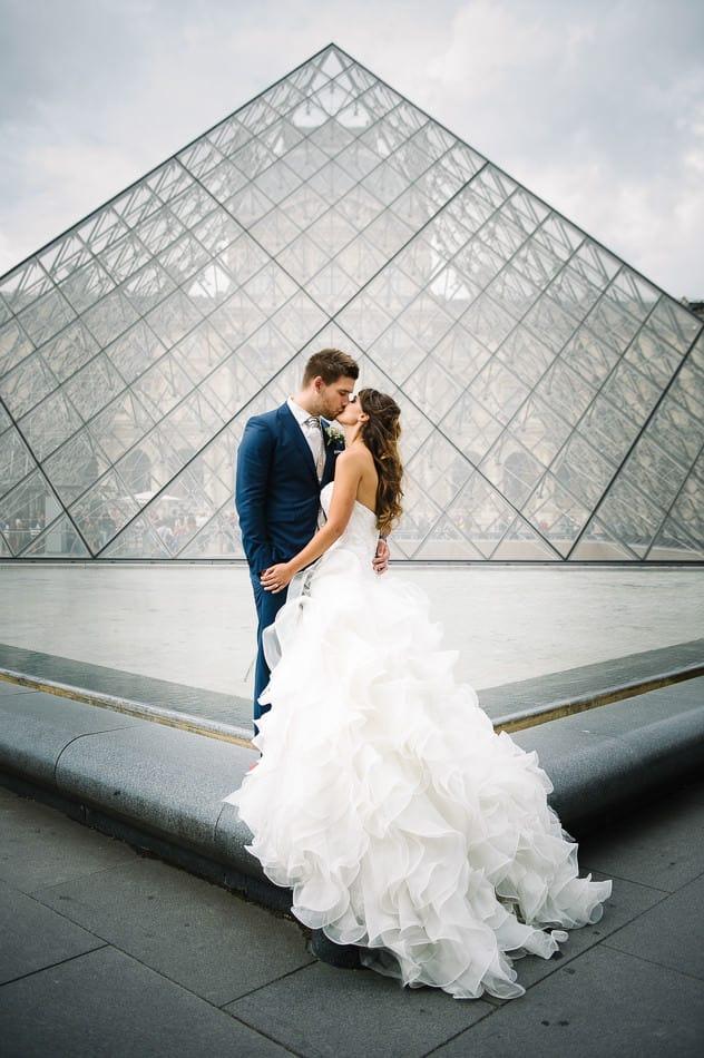 Un couple s'embrasse devant les pyramides du Louvre