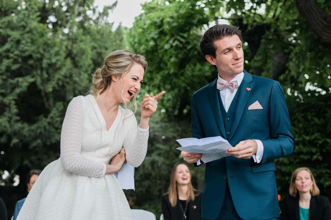 La mariée rit en pointant un invité du doigt